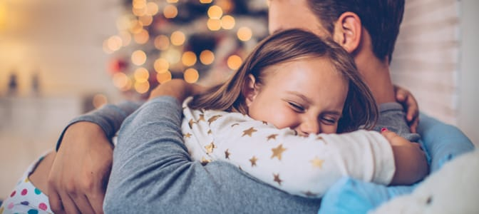 A father embracing his young dauther. In the background, a decorated christmas tree.