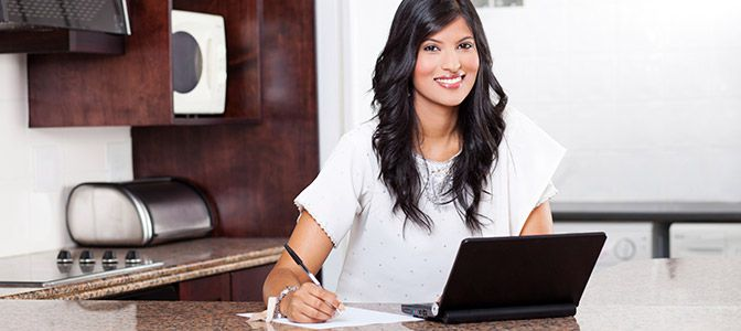 A professional womain sitting in front of a laptop with a pen in hand resting on top of paperwork.