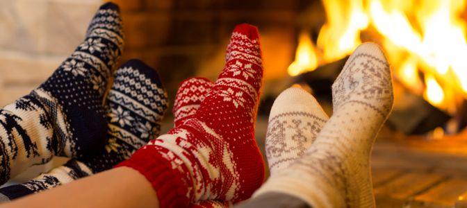 Three people wearing holiday socks near a fire