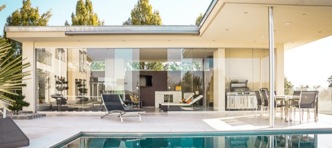 A family grouped together holding keys to a home.