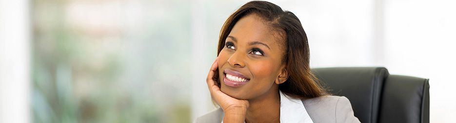 A professional woman pondering with a big smile while sitting at a desk