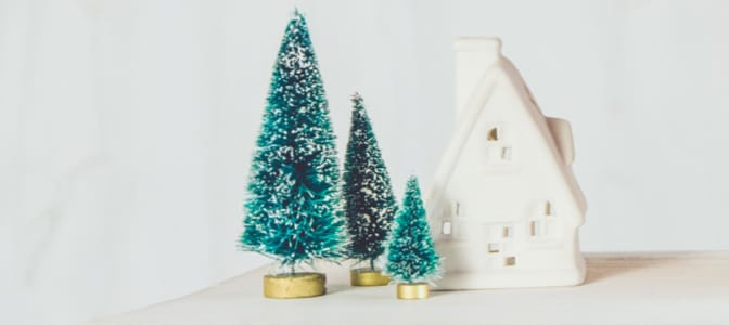 Small scale christmas trees and a cottage resting on a white table. To the left, the words: most wonderful time of the year.