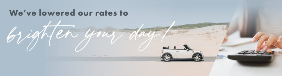 A BMW Mini Cooper parked on the beach. At the top, the words: We've lowered our rates to brighten your day!