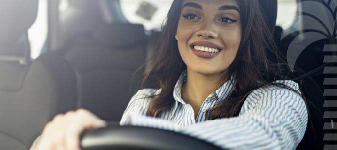 A young woman smiling while driving a car.