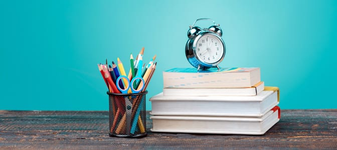 A silver alarm clock resting on a stack of books.