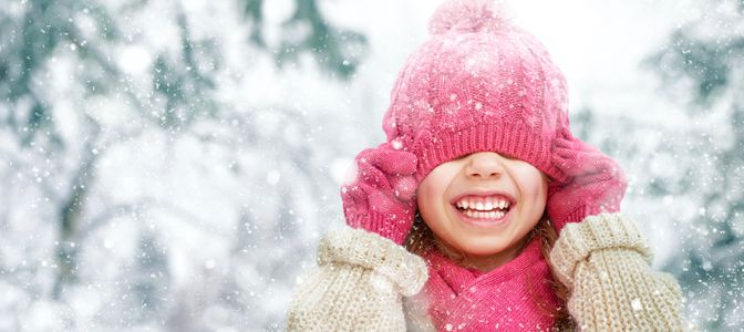 A young girl pulling a pink skully over her head while getting snowed on.