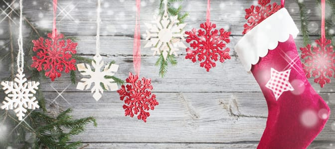 A red stocking and glimmering red and white snow flakes hanging against a gray wooden wall.