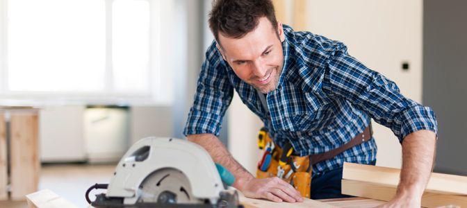 A handyman working over a bench using a wood cutter.