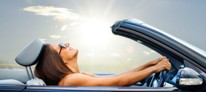 A woman driving in a convertible with the top down.