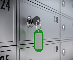A key with a green keychain tag opening a safety deposit box