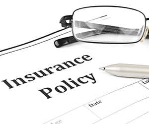 Reading glasses and a silver pen laying on top of an Insurance Policy document