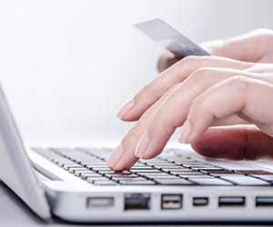 Hands typing on a laptop and holding a card